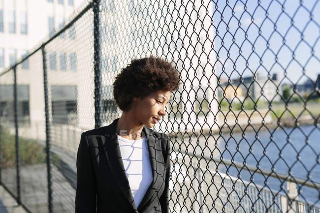 Задумчивая деловая женщина смотрит через сетку проволоки забор — стоковое фото