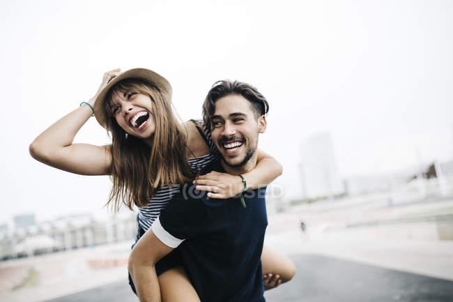 Jeune homme donnant à sa petite amie une balade à dos de cochon — Photo de stock