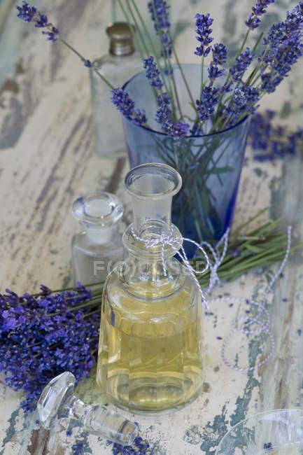 Масло лаванди в пляшку з квітами на пошарпаний деревини — стокове фото