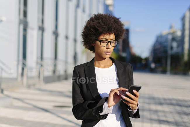 Business woman using smartphone outdoors — стоковое фото