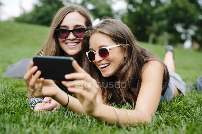 Two happy friends in a park looking at cell phone — Stock Photo