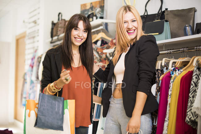 Young women in fashion boutique shopping for clothes — Stock Photo