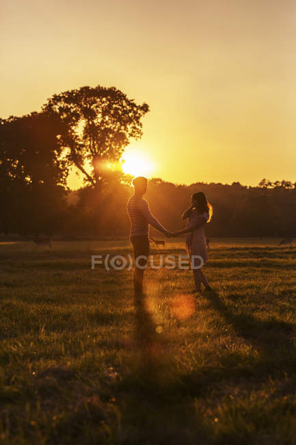 Couple with deers on a meadow at sunset — Stock Photo