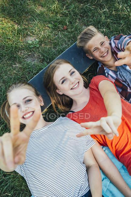 Три щасливі підліткової друзів, лежачи на скейтборді у лузі робить знак перемоги — стокове фото