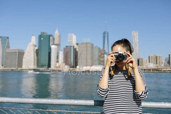 USA, New York City, young woman standing in front of skyline taking a photo with camera — Stock Photo