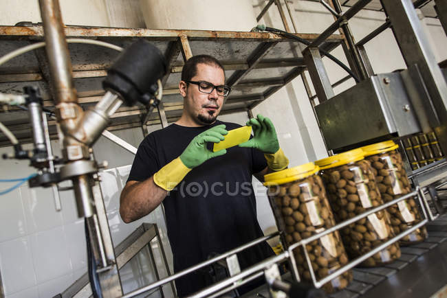 Man in factory taking smartphone picture at conveyor belt with filled olive glasses — Stock Photo