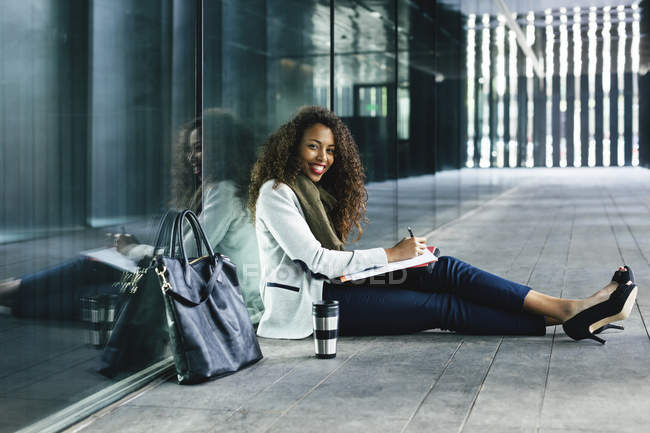 Smiling young businesswoman with coffee to go mug and folder sitting outdoors — Stock Photo