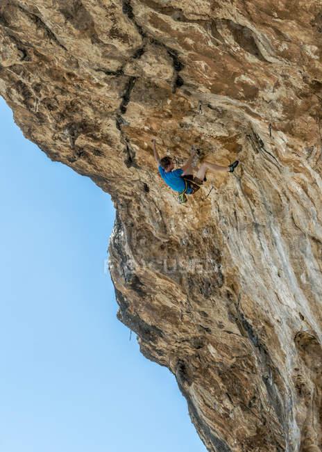Malte, Ghar Lapsi, Grotte McCartheys, escalade sur falaise avec ciel bleu en arrière-plan — Photo de stock