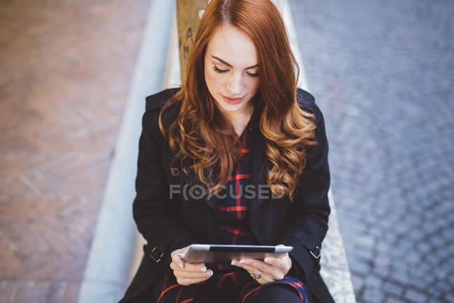Молода жінка, дивлячись на цифровий планшет на відкритому повітрі — стокове фото