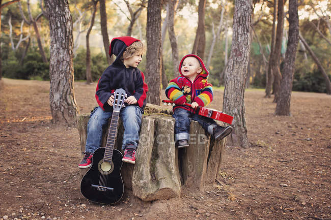 Little boy and baby brother with guitars in a forest — Stock Photo