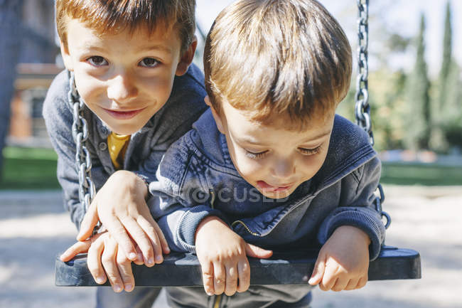 Two happy boys on a swing at the playground — Stock Photo