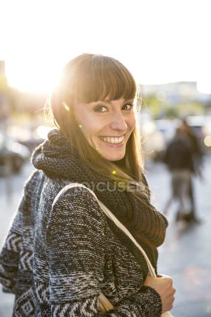 Портрет улыбающийся молодой женщины, просмотр через ее плечо — стоковое фото