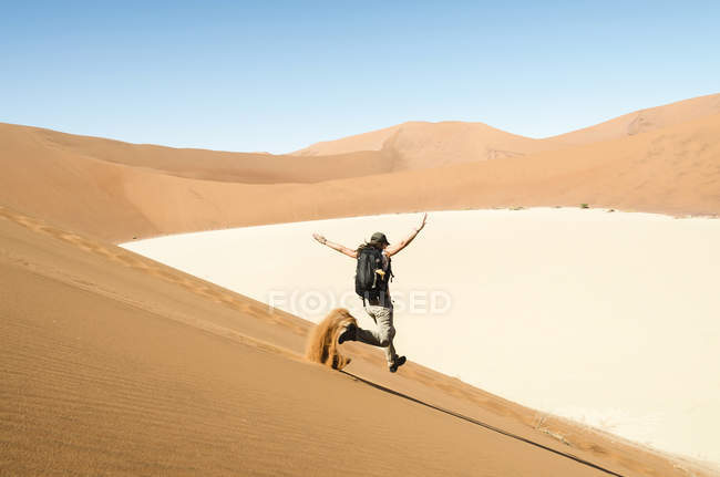 Namibia, Namib Desert, woman running down a dune on the way to Deadvlei — Stock Photo