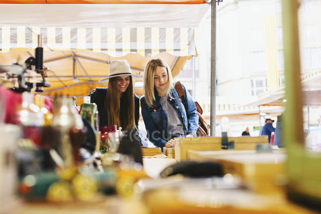 Two young women standing at a stall on flea market — Stock Photo