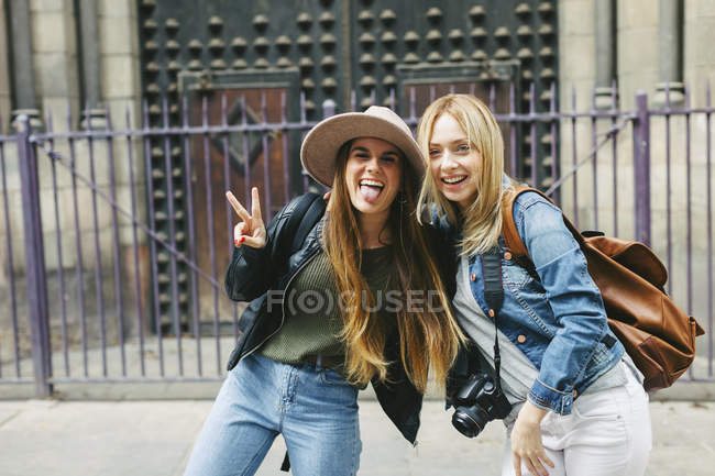 Spain, Barcelona, two playful young women in front of entrance portal — Stock Photo
