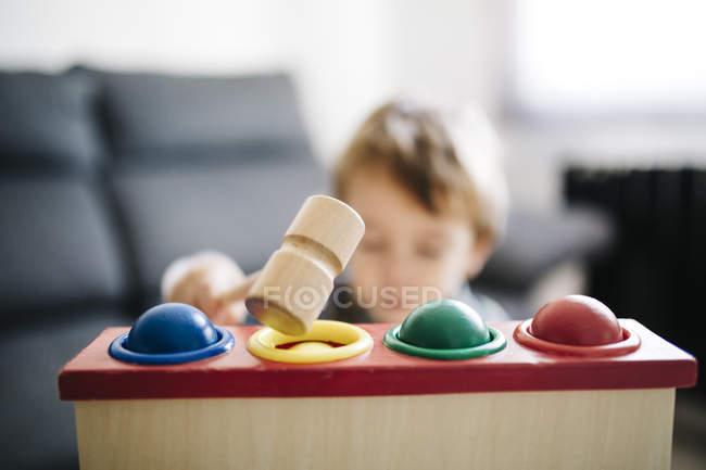 Ragazzo che gioca con giocattolo abilità motoria in legno — Foto stock