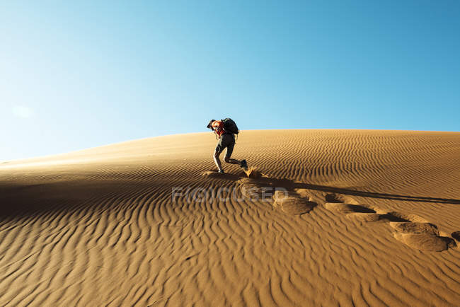 Namibia, Namib Wüste, Sossusvlei, Mann Klettern eine Dünen bei Sonnenuntergang — Stockfoto