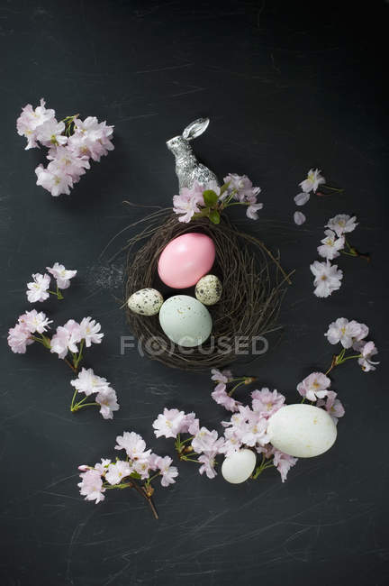 Easter nest with eggs, silver Easter bunny, feathers and cherry blossoms — Stock Photo