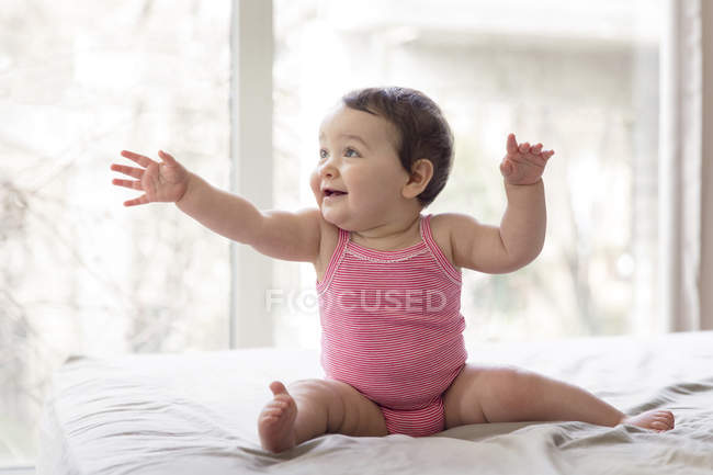 Smiling Baby Girl Sitting On Bed In Front Of A Window And Reaching Out Arm U2014