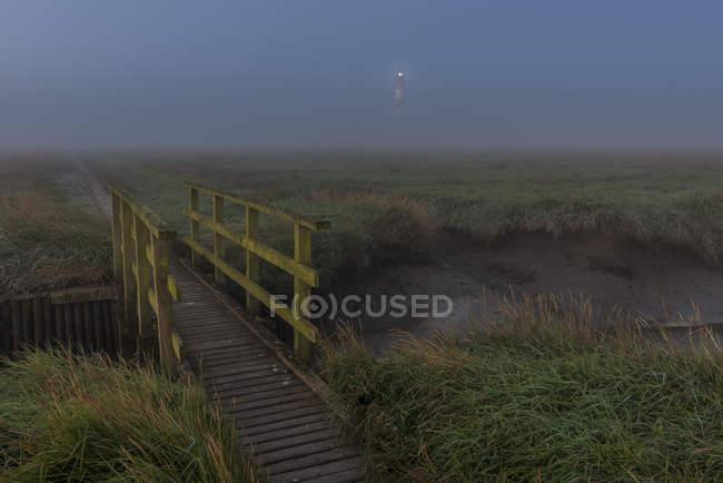 Germany, Schleswig-Holstein, North Sea Coast, Westerheversand Lighthouse, bridge and fog — Stock Photo
