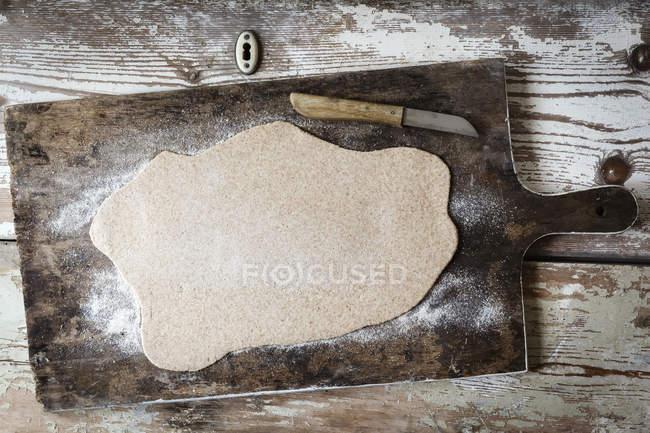 Extendió la masa y el cuchillo en una tabla de madera - foto de stock