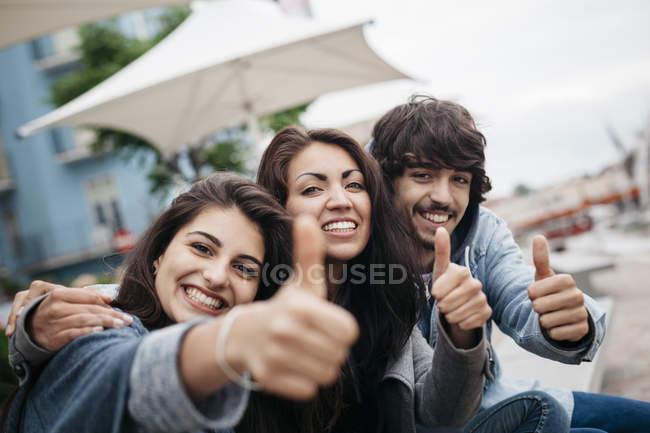 Portrait de trois amis heureux à l'extérieur avec les pouces levés — Photo de stock