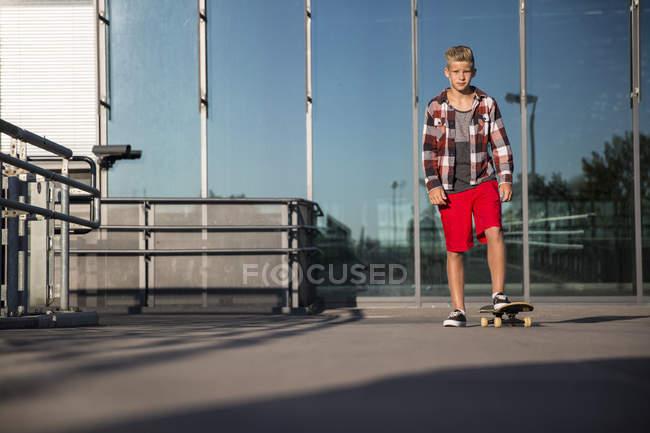 Caucasian teenager boy riding on skateboard — Stock Photo