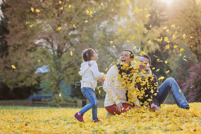 Игровая семья в осеннем парке — стоковое фото