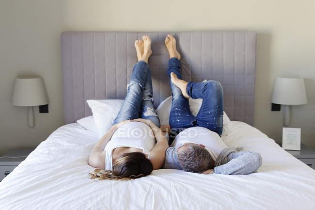 Hombre y esposa embarazada relajante en cama - foto de stock