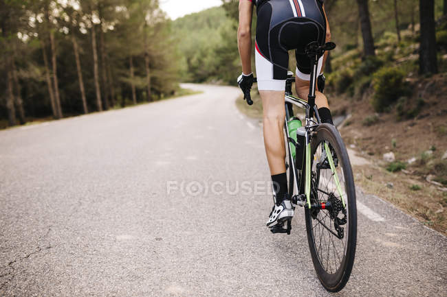 Cyclist riding racing cycle on road — Stock Photo