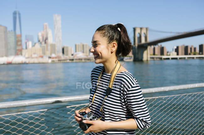 USA, New York, giovane donna sorridente con macchina fotografica — Foto stock