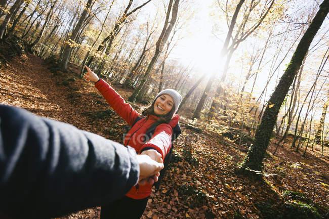 Femme souriante dans les bois tenant la main de l'homme — Photo de stock