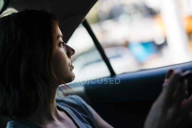 Profil de jeune femme assise à l'intérieur d'une cabine — Photo de stock