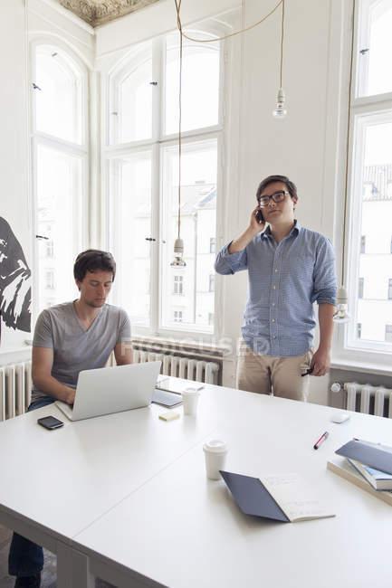 Dois empresários criativos com laptop e celular em um escritório moderno — Fotografia de Stock