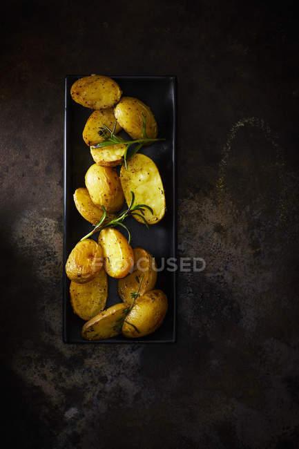 Assiette de pommes de terre cuites au four avec jéjé sur métal rouillé — Photo de stock