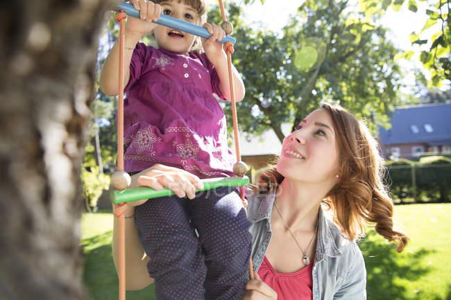 Mutter beobachtet Tochter auf Strickleiter im Garten — Stockfoto