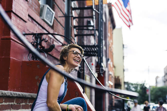 USA, New York City, Williamsburg, portrait of happy blond woman sitting on the stairs — Stock Photo