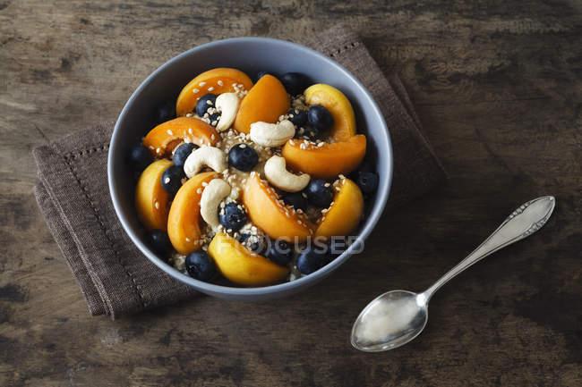 Ciotola di muesli con grano saraceno incrinato, frutta, sesamo e anacardi — Foto stock