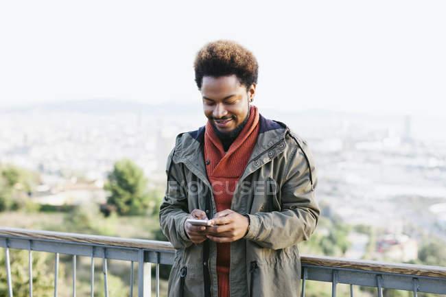 Портрет улыбающегося молодого человека, смотрящего на свой смартфон — стоковое фото