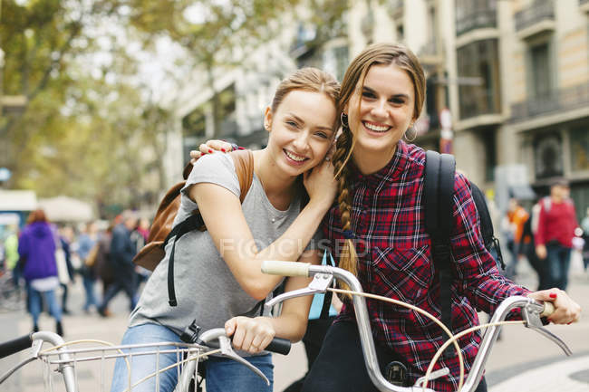 Two young women on bicycles in the city — Stock Photo