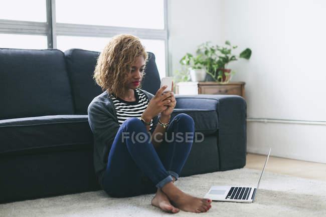 Женщина сидит на ковре и использует смартфон — стоковое фото