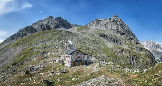 Switzerland, Valais, Wiwannihorn, Wiwanni hut on hills over grass — Stock Photo