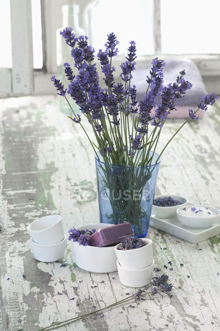 Lavender in vase with bath salts and lavender soap in bowls — Stock Photo