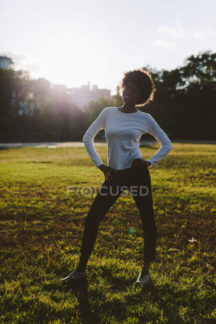Smiling young woman standing with hands on her hips on a meadow of a park at backlight — Stock Photo
