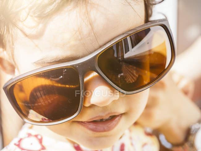 Portrait of little girl wearing oversized sunglasses — Stock Photo