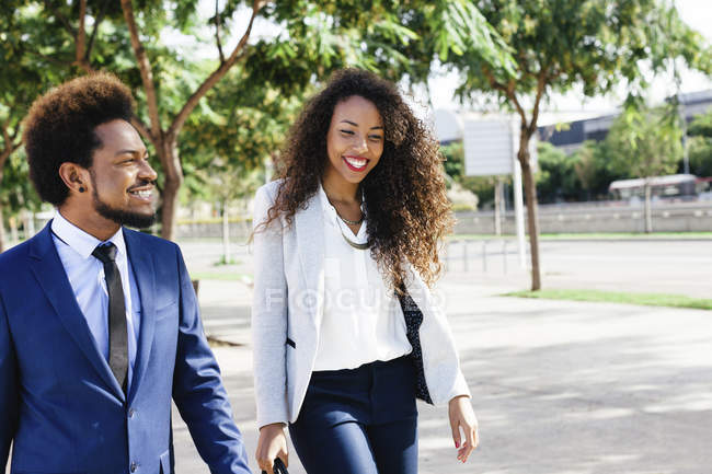 Two smiling young business people walking side by side on street — Stock Photo