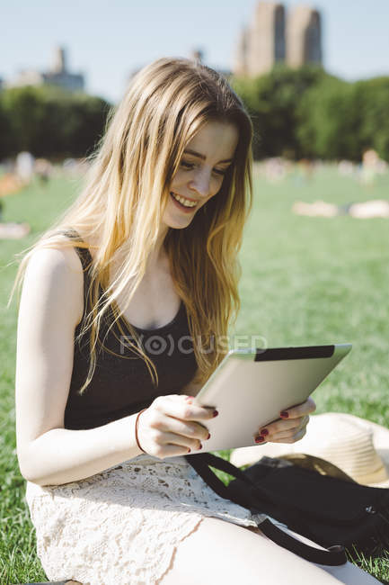 USA, New York City, young woman using digital tablet in Central Park — Stock Photo