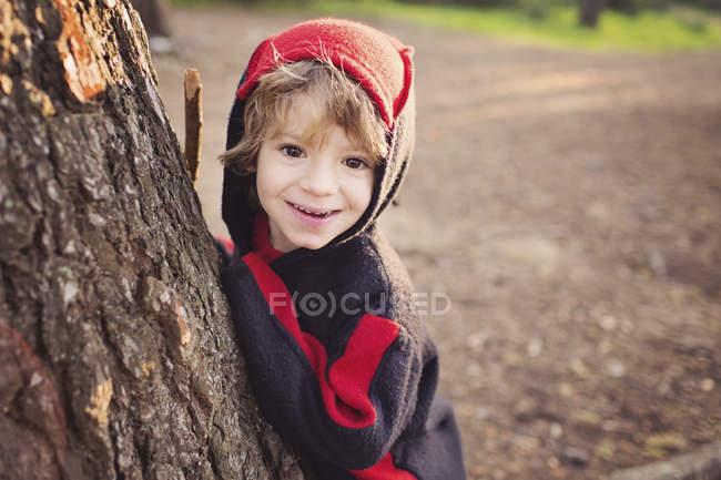 Retrato de menino, casaco com capuz, brincando de esconde-esconde atrás de uma árvore — Fotografia de Stock