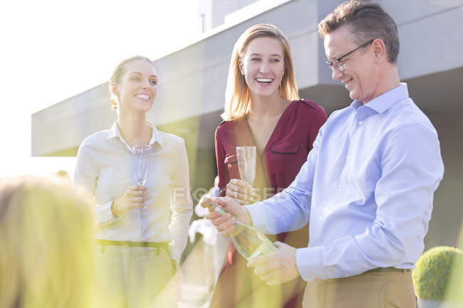 Businessman opening champagne bottle on a company party — Stock Photo