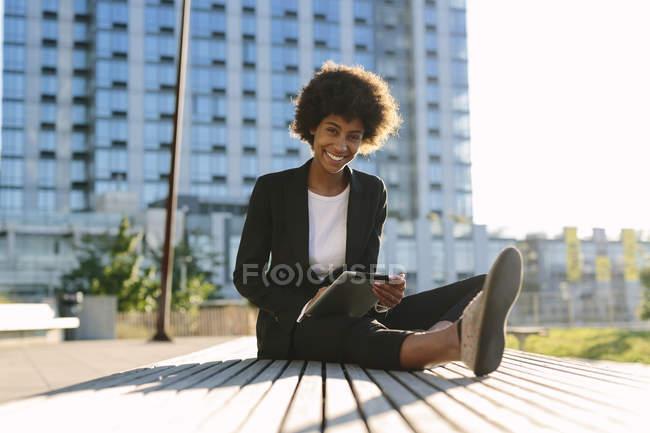 Portrait de femme d'affaires assise sur un banc avec tablette numérique — Photo de stock